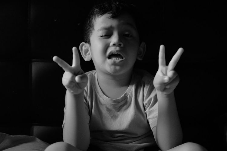 Close-Up Portrait Of Boy Showing Peace Sign While Sitting In Darkroom