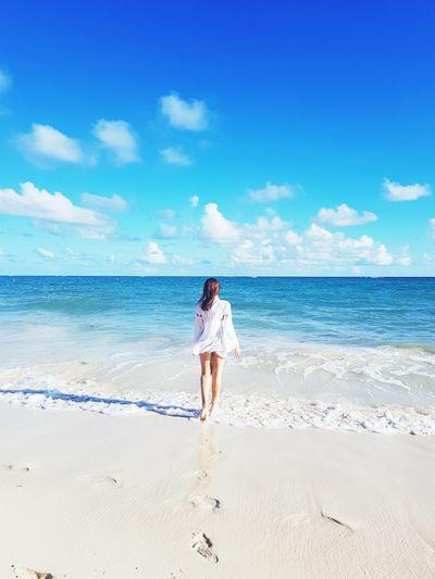 Full Length Rear View Of Woman Walking Towards Sea On Shore At Beach Against Sky