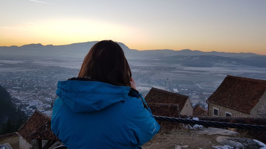 Rear view of woman looking at snowcapped mountains during sunset