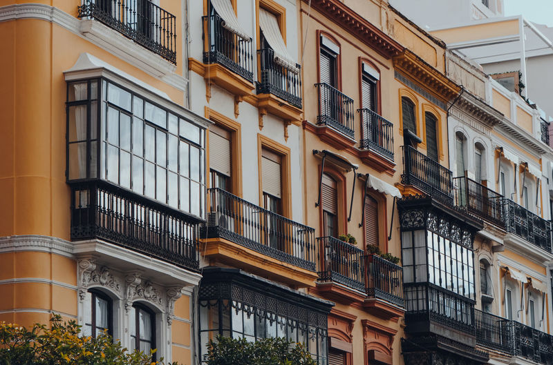 Close up of a row of traditional apartment blocks on a street in seville, andalusia, spain.
