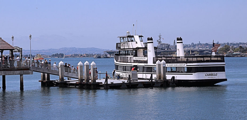 """The Ferry Boat Landing on Coronado Island is a popular tourist landing. Before the Coronado Bridge was built, the Ferry was the only way to get to the Island. The Harbor was alive with Ferrry's, from vehicle carriers, to people carriers, and hundreds of """"nickle snatchers."""" Today, the Ferry is an inexpensive and enjoyable way to get that skyline view of America's Finest City, San Diego, California. Ferry, Ferry Landing, Pier, Boat, Skyline, Cityscape, City, Harbor, Bay, Cruise, People, Tourist, San Diego, California, Day Nature Outdoors Sea Sky Water"""