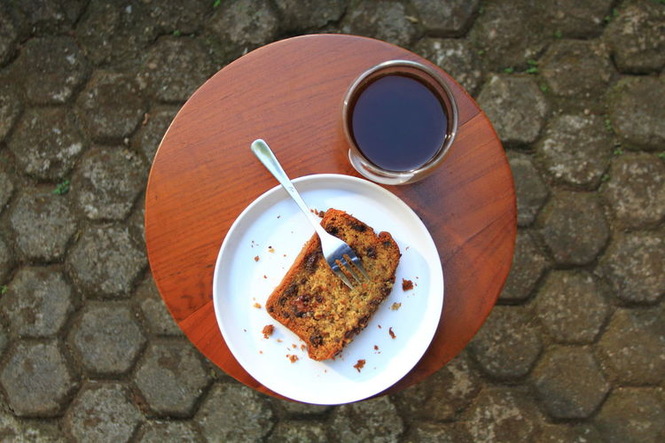 A slice of banana bread on white plate and a cup of  coffee for breakfast on table