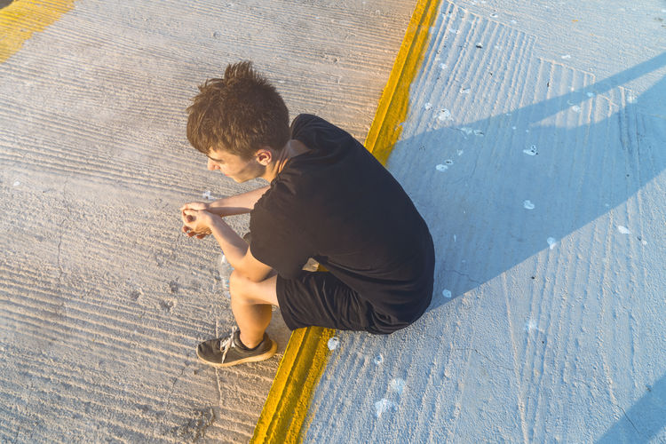 High angle view of boy sitting on floor