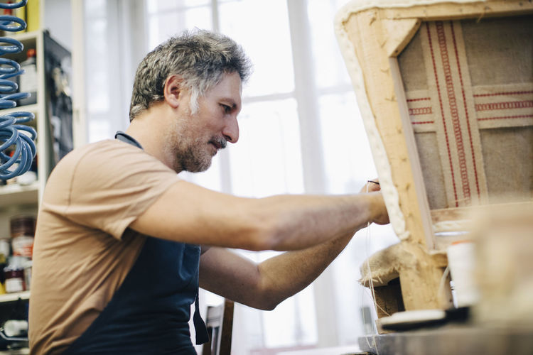 Mature craftsperson making furniture in workshop