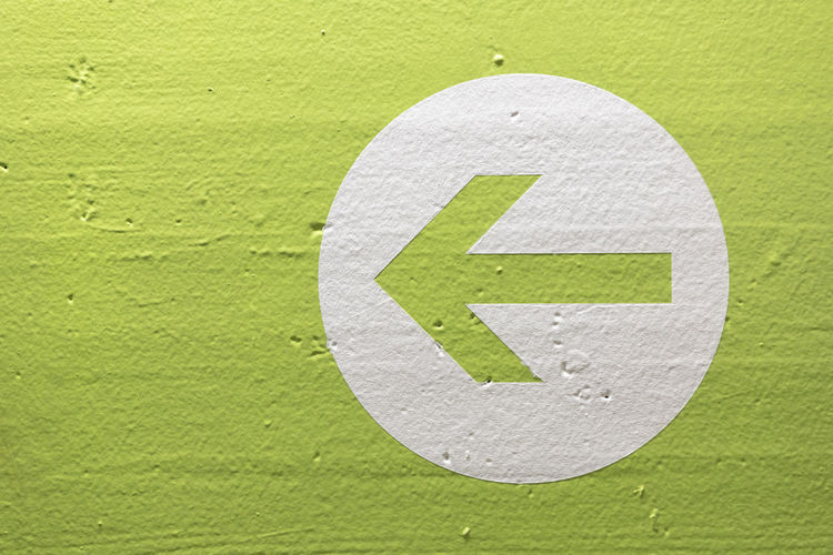 Close-up of arrow sign on wall