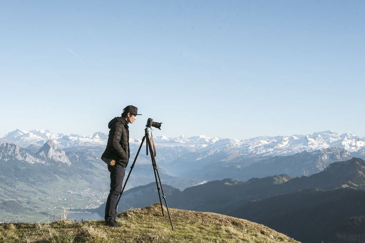Young man photographing while standing on mountain against sky