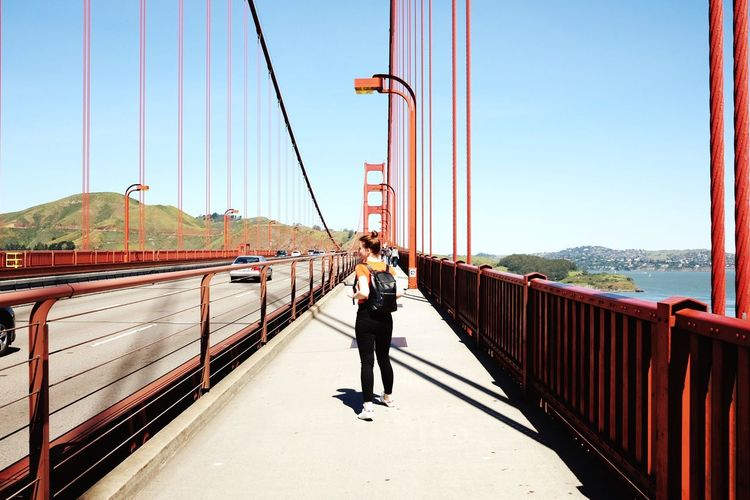 Rear view of woman walking on golden gate bridge against blue sky