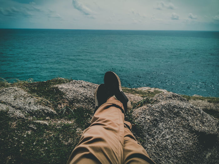 Low section of man relaxing on rock formation by sea