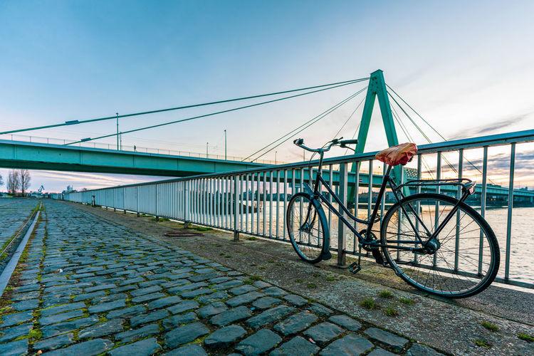 Bicycle on bridge against blue sky