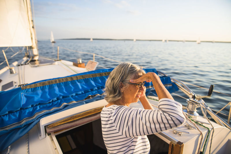 Rear view of woman on sailboat in sea against sky