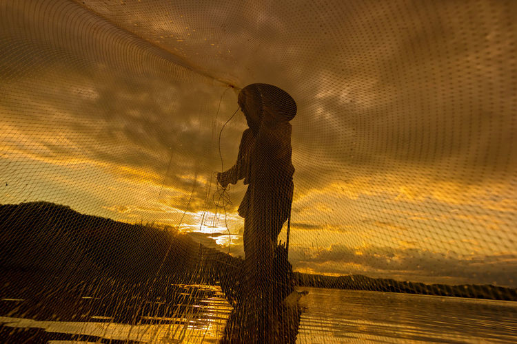 Man Throwing Fishing Net In Sea At Sunset