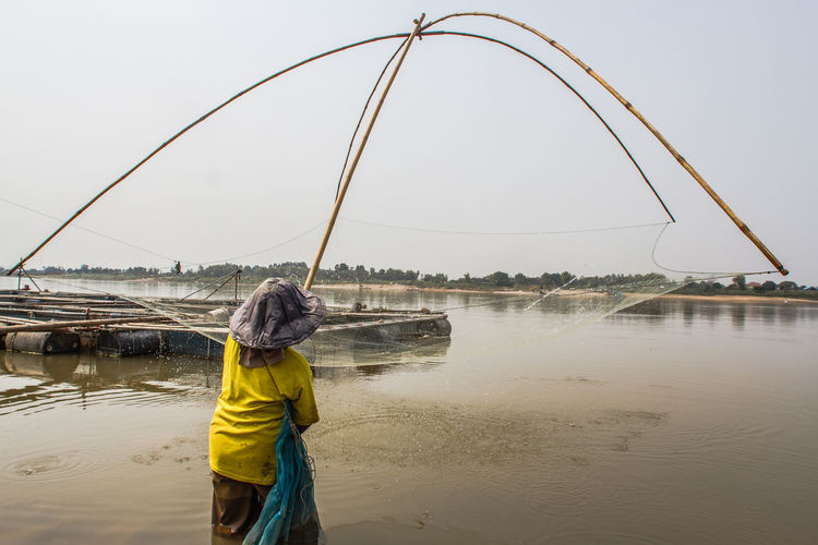 Rear view of man fishing in river against clear sky