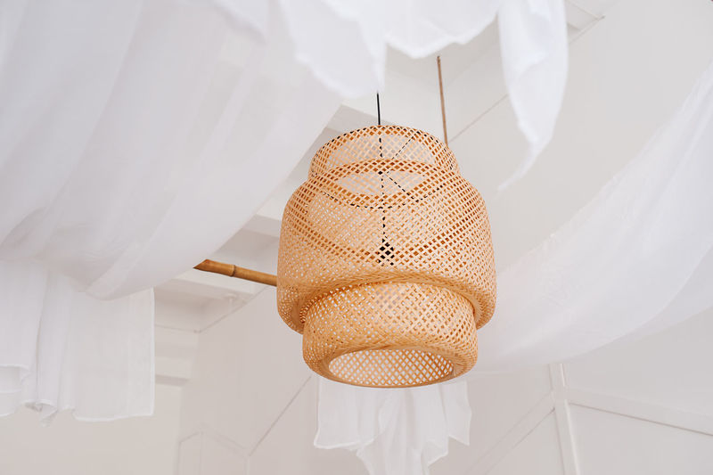 A stylish wicker wooden chandelier in boho and bali style hangs on the ceiling