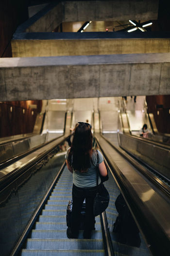 Rear view of woman on escalator
