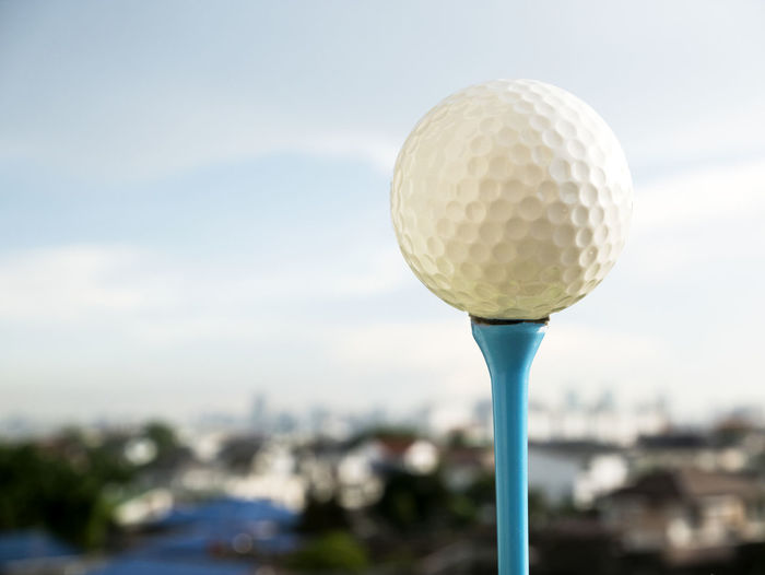 Close-up of golf ball on tee against sky
