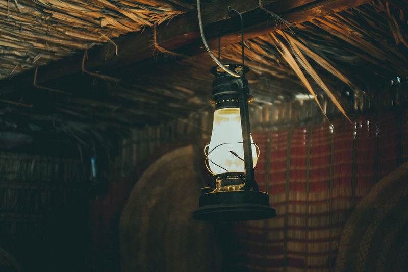 Illuminated Lamp Hanging On Ceiling In Hut