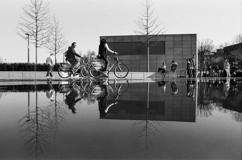 ANALOG; Rollei RPX 100 The Week on EyeEm Light And Shadow Capture The Moment Film Photography Rollei Analogue Photography Nikonphotography Street Photography Monochrome Black And White Bnw Spring Filmisnotdead Grain Reflection Sky Tree Nature Built Structure Day Architecture Men Real People Water Outdoors Building Exterior Group Of People People Activity Transportation Bicycle Lake The Art Of Street Photography