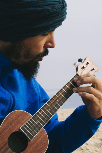 Close-up of man playing ukulele at beach