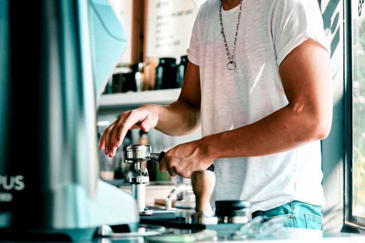 Midsection of man standing by coffee in cafe