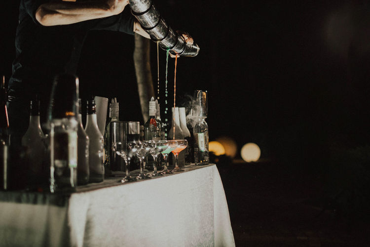 Low angle view of wine glass bottles and barmen show