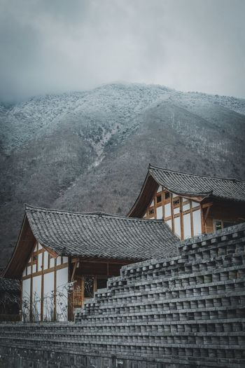 Architecture Built Structure Building Exterior Building Roof Mountain No People House Nature Cold Temperature Winter Sky Day Residential District Snow Outdoors Mountain Range Religion Tree Roof Tile Cottage Travel