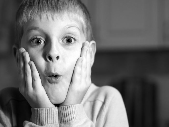 Close-up portrait of shocked boy at home