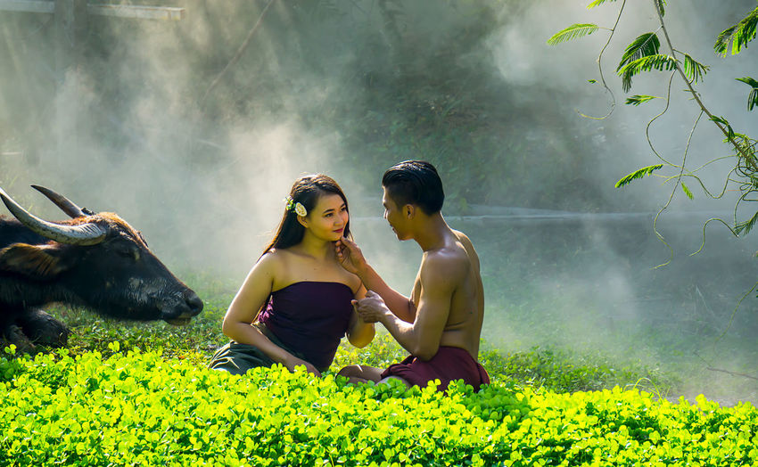 Smiling young couple romancing on grassy field