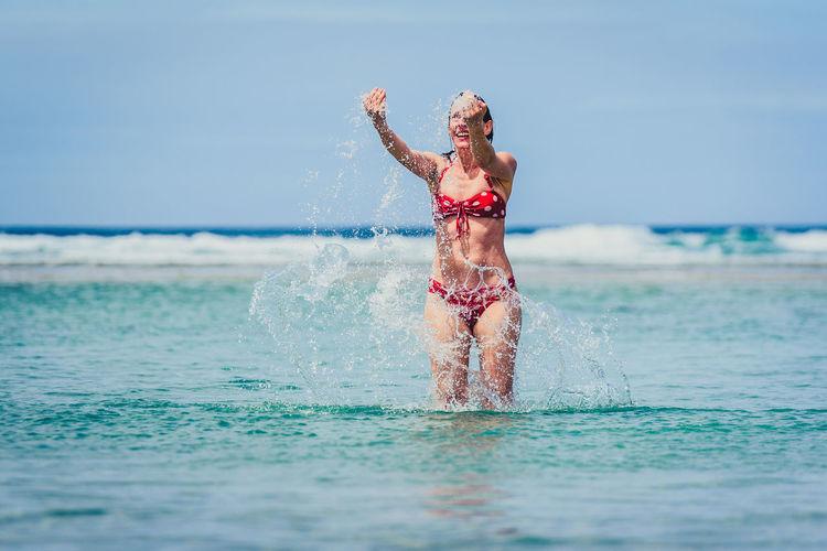 Happy mid adult woman splashing water in sea against sky