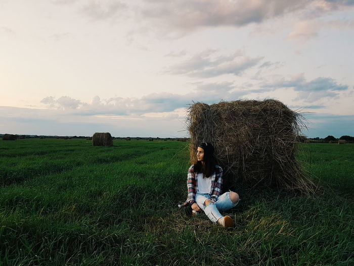Young Woman Sitting On Grassy Field During Sunset