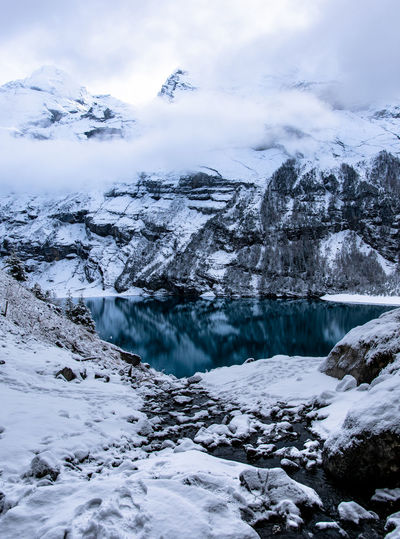 Lake Amidst Snowcapped Mountains Against Sky