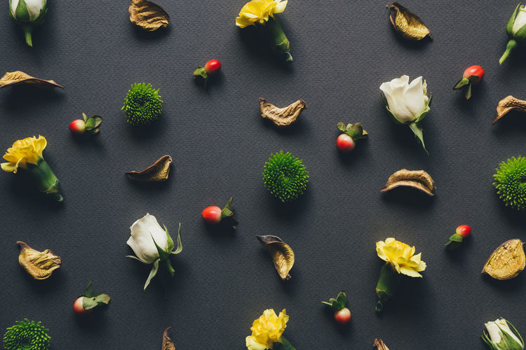 High Angle View Of Flowers With Fruits And Leaf Arranged On Table