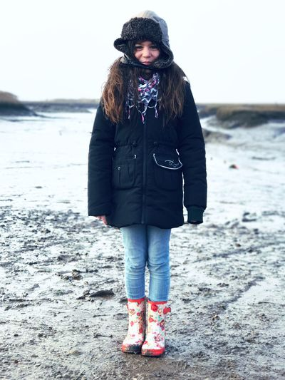 Full length of girl standing on snow covered beach