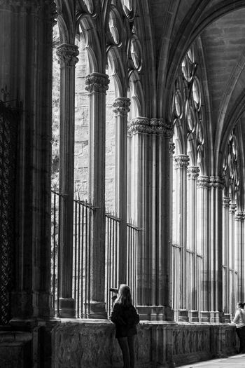 Rear view of women standing in cathedral corridor