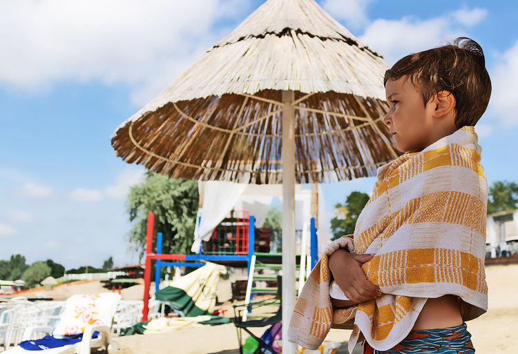 Side view of a boy holding umbrella against sky