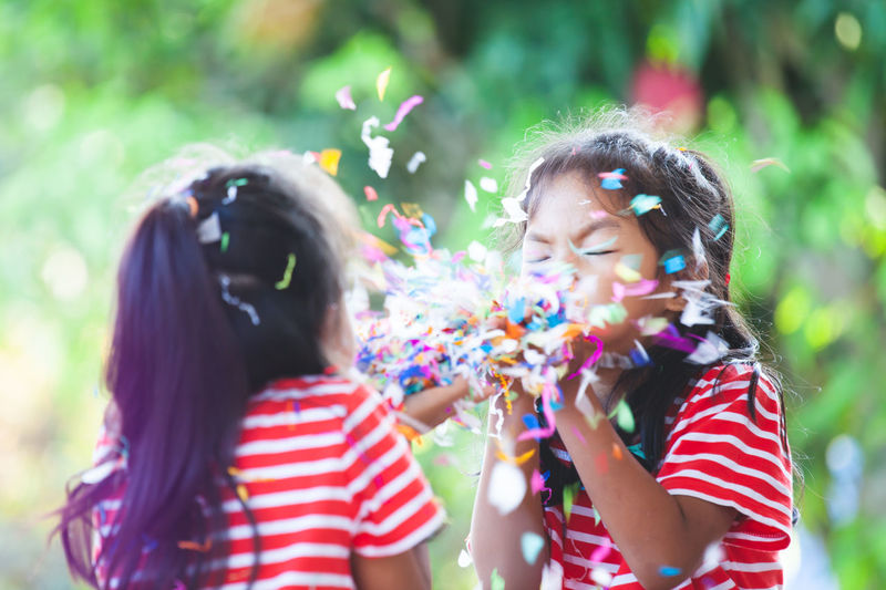 Sisters blowing confetti outdoors