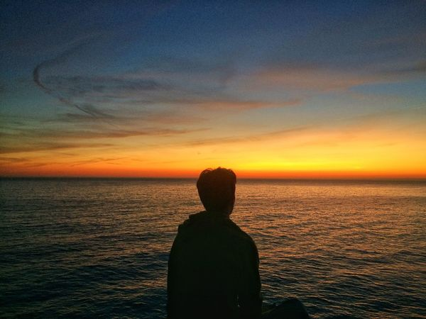 Sunset Sea Water Scenics Horizon Over Water Beauty In Nature Nature Orange Color Sky Rear View Real People Silhouette One Person Tranquil Scene Idyllic Lifestyles Tranquility Leisure Activity Looking At View Standing