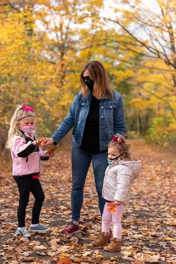Full length of friends standing on autumn leaves