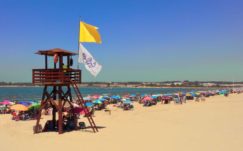 Lifeguard tower with yellow flag. Clear Sky Coastline Colors Colours Vacations Beach Blue Colorful Crowd Day Flags Jellyfishes Large Group Of People Leisure Activity Lifeguard Post Lifeguard Tower Real People Sand Sea Summer Surveillance Umbrellas Watching Yellow Yellow Flag