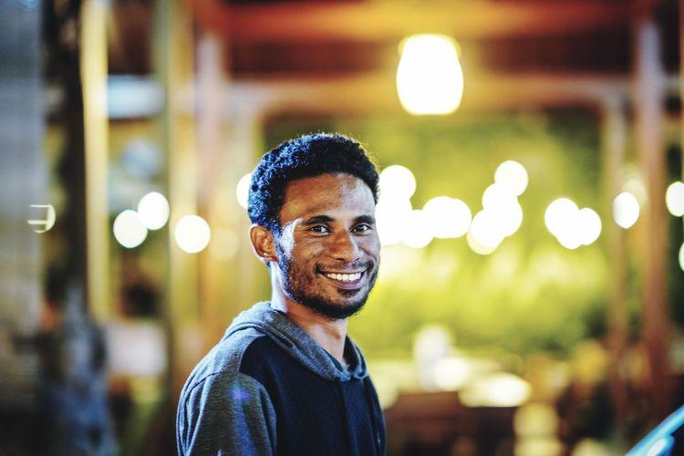 Portrait of smiling man standing illuminated restaurant at night