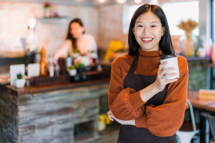 Portrait of smiling barista holding coffee cup while standing in cafe