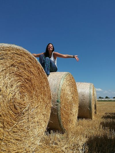 Low Angle View Of Young Woman Sitting On Hay Bale