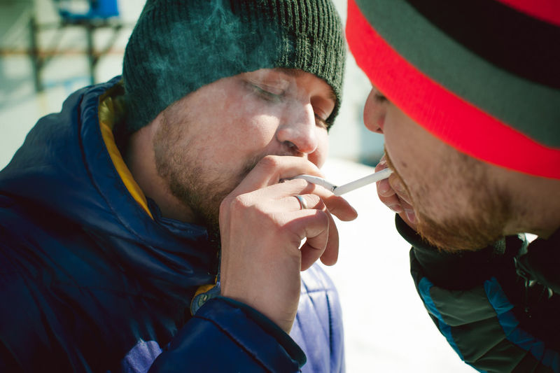 Close-up of men in warm clothing smoking cigarette