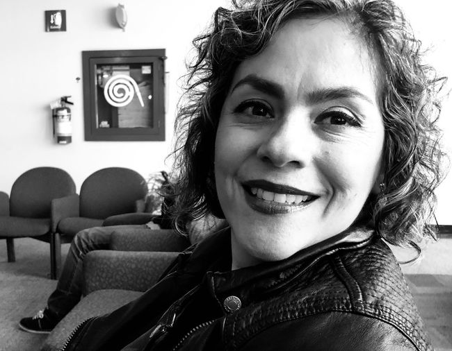 Portrait of smiling mid adult woman sitting in waiting room