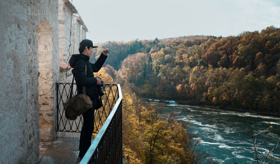 Man photographing while standing by railing