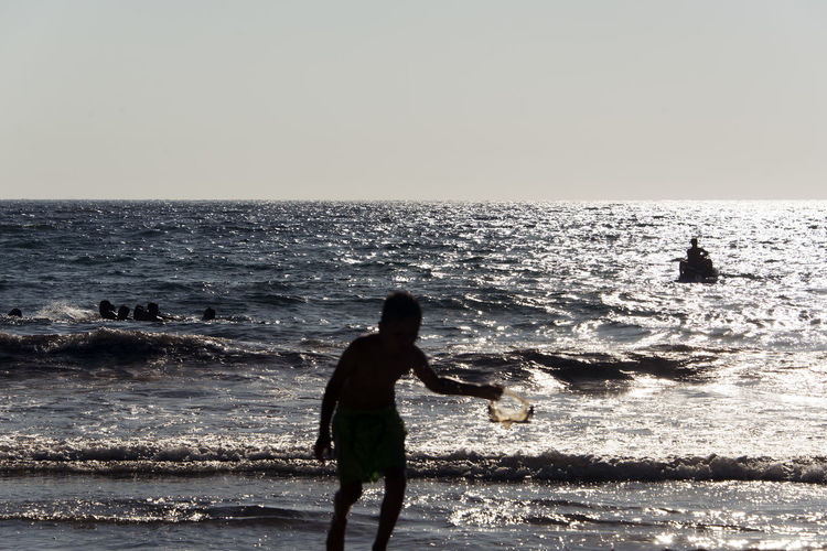 Silhouette of People playing, swimming in the waves in the island of Patmos, Greece in summer time Beach Beauty In Nature Horizon Horizon Over Water Land Leisure Activity Lifestyles Men Motion Nature Outdoors People Real People Scenics - Nature Sea Silhouette Sky Standing Water Wave