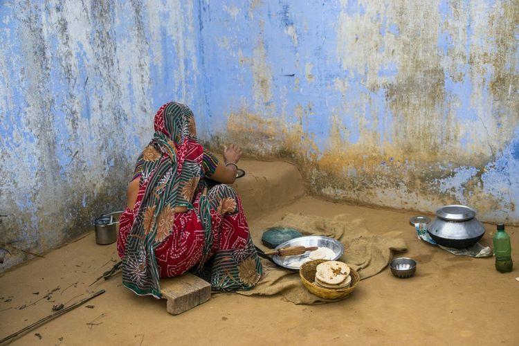 Rear View Of Woman In Sari Preparing Chapatti Outdoors