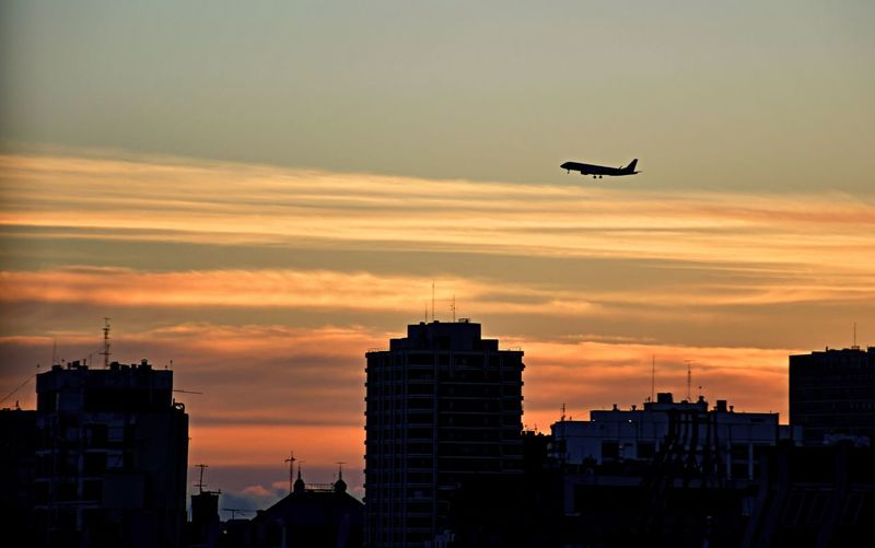Silhouette of airplane flying over buildings against sky during sunset