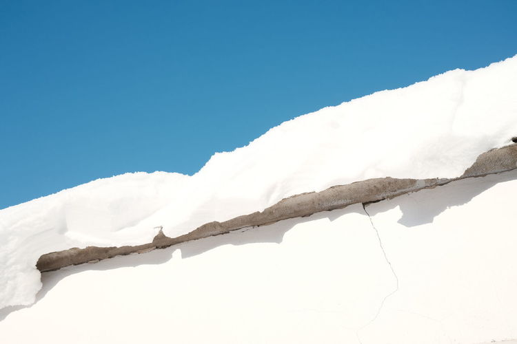 Low angle view of snow against clear blue sky