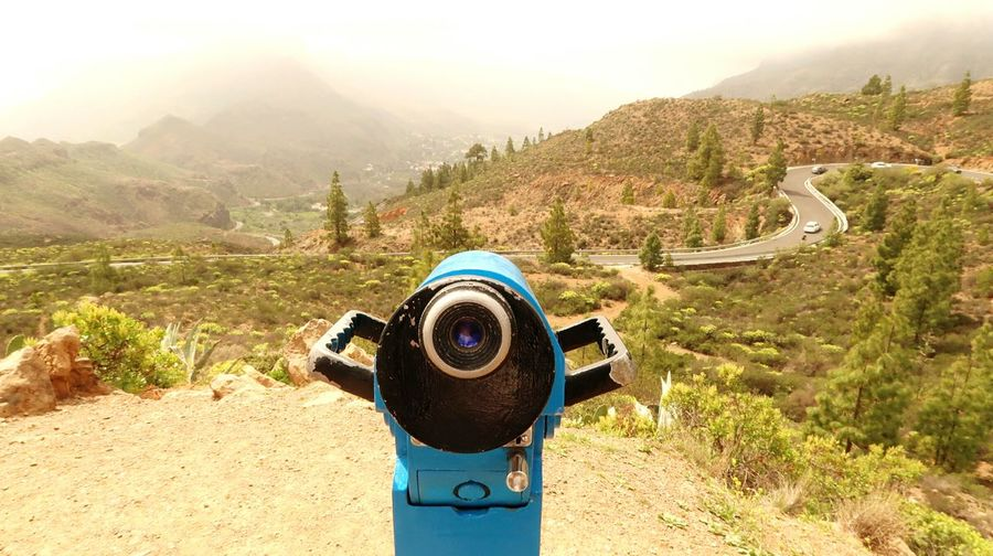 Coin-operated binoculars on mountain against sky