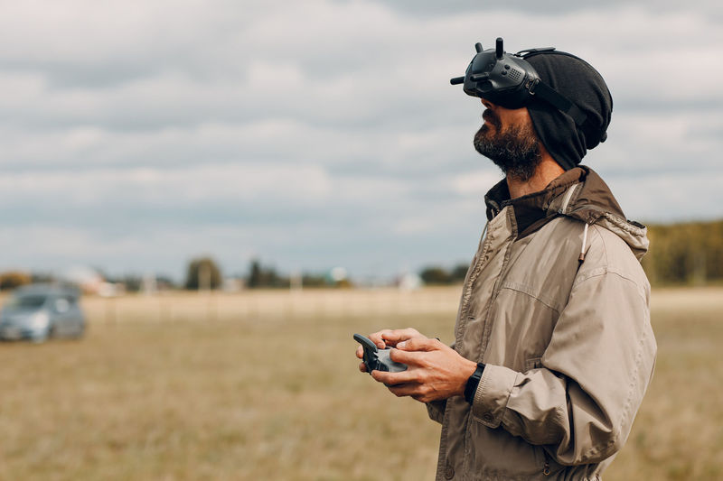 Man holding camera while standing on field against sky
